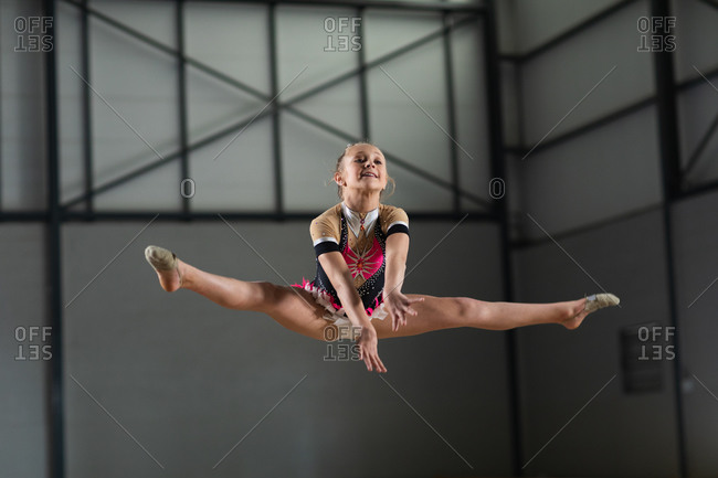 Front view of teenage Caucasian female gymnast performing at the gym, jumping and doing split, wearing pink and beige leotard
