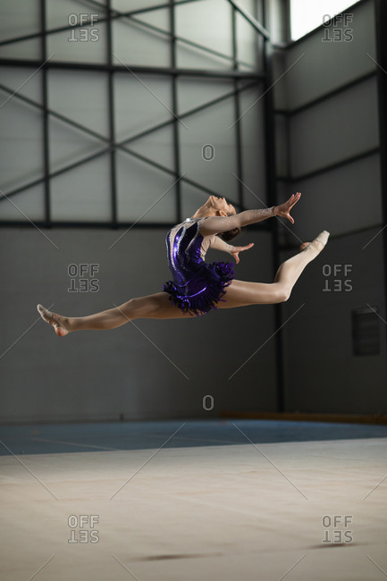 Side view of teenage Caucasian female gymnast performing at the gym, jumping and doing split, wearing purple leotard. Gymnasts training hard for competition.