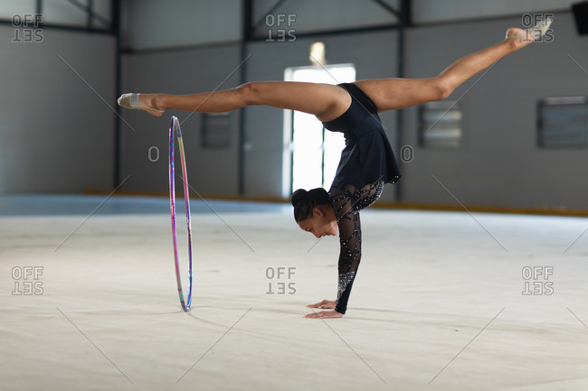 Side view of teenage mixed race female gymnast performing at the gym, exercising with a hoop, doing handstand and split, wearing black leotard