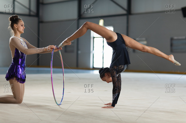 Side view of teenage Caucasian and mixed race female gymnasts performing at the gym, exercising with a hoop, girl in purple leotard holding the hoop, girl in black leotard doing handstand and split