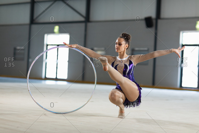 Front view of teenage Caucasian female gymnast performing at the gym, exercising with a hoop, crouching with one leg out, holding the hoop, wearing purple leotard