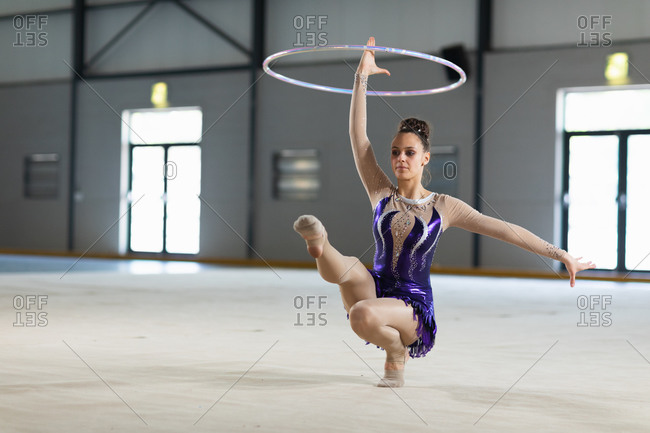 Front view of teenage Caucasian female gymnast performing at the gym, exercising with a hoop, crouching with one leg out, swinging the hoop, wearing purple leotard