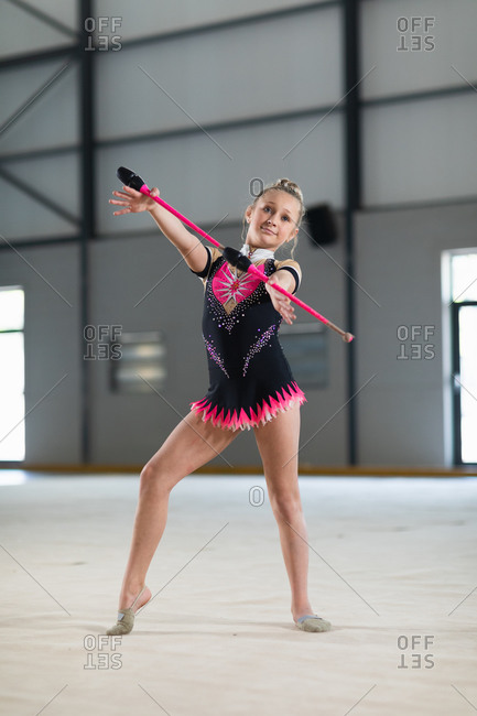 Front view of teenage Caucasian female gymnast performing at the gym, exercising with a pink baton, smiling and wearing black and pink leotard