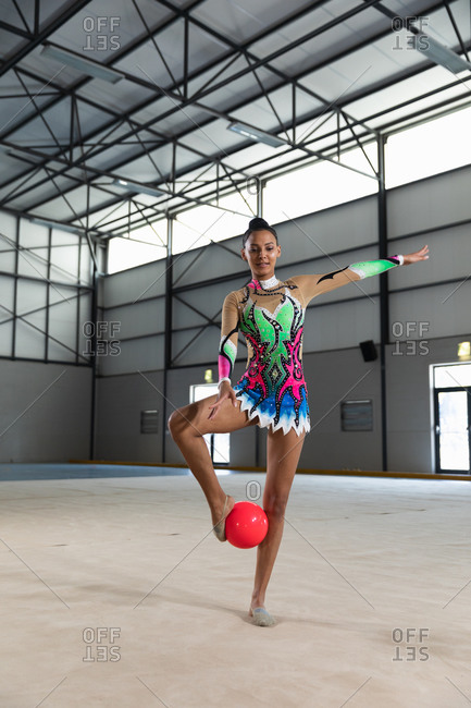 Front view of teenage mixed race female gymnast performing at the gym, exercising with a red ball, standing with the ball between her feet, wearing multi colored leotard