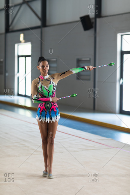Front view of teenage mixed race female gymnast performing at the gym, exercising with clubs, holding clubs, one arm outstretched, concentrating, wearing multi colored leotard
