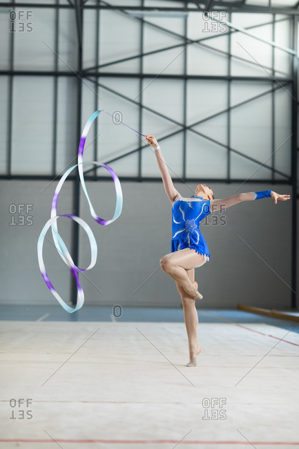 Front view of teenage Caucasian female gymnast performing at the gym, exercising with ribbon, standing on one leg, one arm outstretched, looking at camera, wearing blue leotard