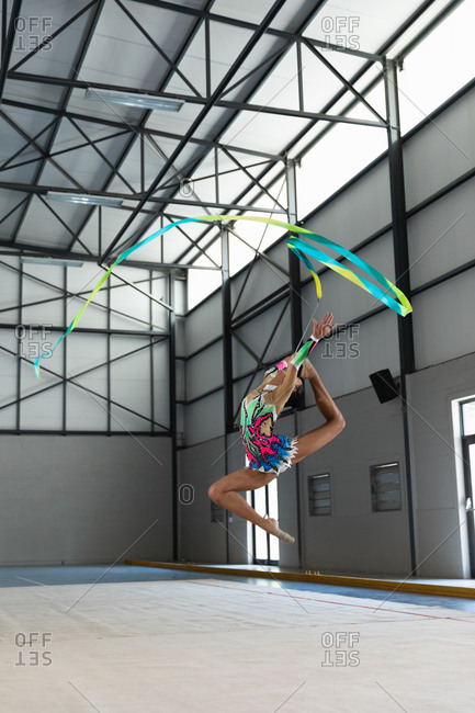 Side view of teenage mixed race female gymnast performing at the gym, exercising with ribbon, jumping, wearing multi colored leotard