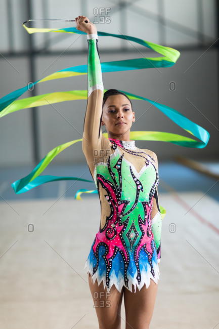 Front view close up of teenage mixed race female gymnast performing at the gym, exercising with ribbon, wearing multi colored leotard