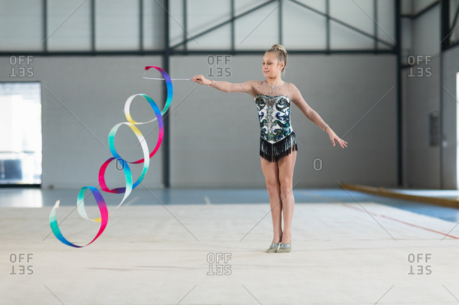 Front view of teenage Caucasian female gymnast performing at the gym, exercising with ribbon, wearing multi colored leotard. Gymnasts training hard for competition.