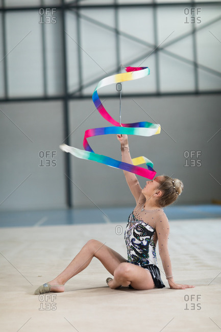 Side view of teenage Caucasian female gymnast performing at the gym, exercising with ribbon, wearing multi colored leotard. Gymnasts training hard for competition.
