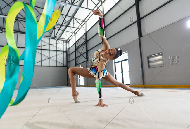 Side view of teenage mixed race female gymnast performing at the gym, exercising with ribbon, bending backwards and leaning on the floor, wearing multi colored leotard