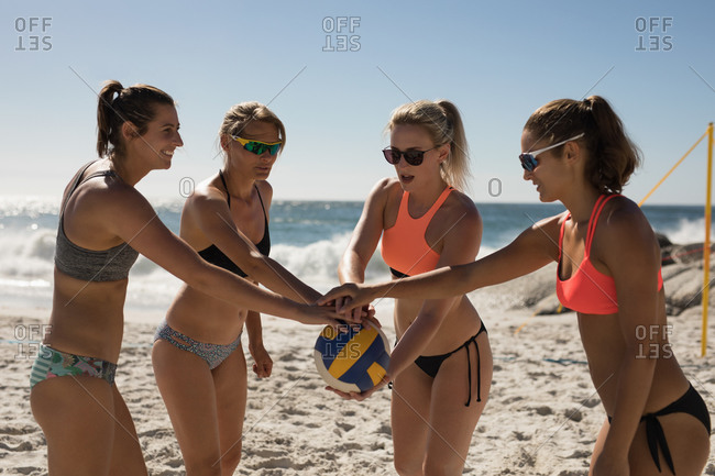 Front view of a group of Caucasian female friends enjoying free time on a beach on a sunny day with blue sky, stacking their hands on a ball together