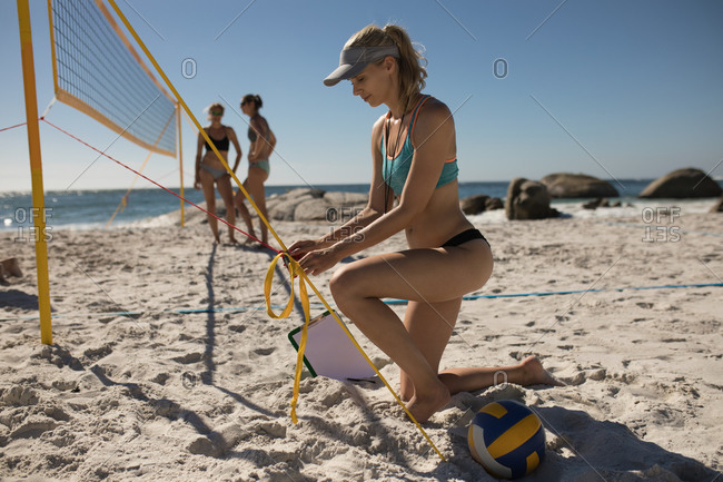 Side view of a Caucasian woman with friends in the background enjoying free time on a beach on a sunny day with blue sky,, preparing net for a game of volleyball