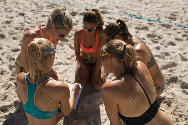 High angle view of a group of Caucasian female friends enjoying free time on a beach on a sunny day, preparing for a game, one of them holding clipboard