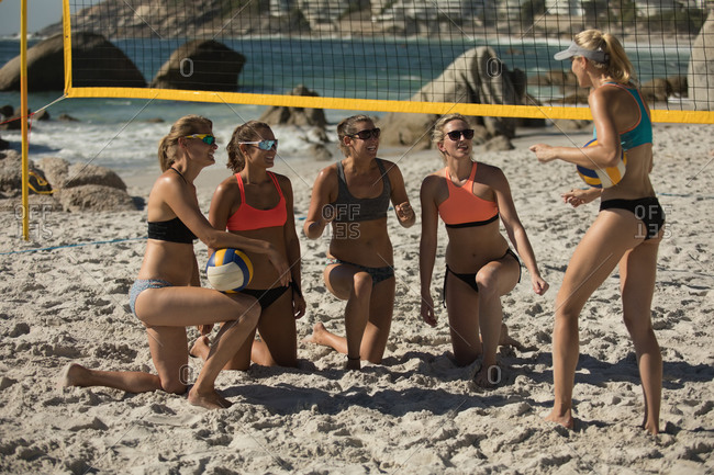 Front view of a group of Caucasian female friends enjoying free time on a beach on a sunny day, two of them holding a ball, one standing and talking