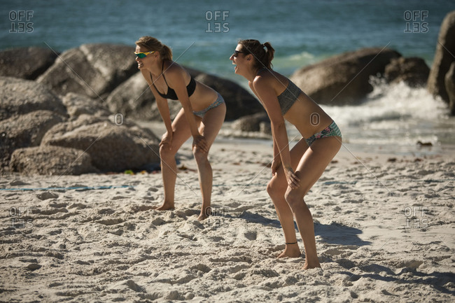 Side view of two of Caucasian female friends enjoying free time on a beach on a sunny day, playing volleyball ready for a ball