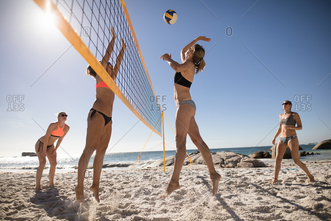 Low angle side view of a group of Caucasian female friends enjoying free time on a beach on a sunny day with blue sky, playing volleyball, hitting a ball