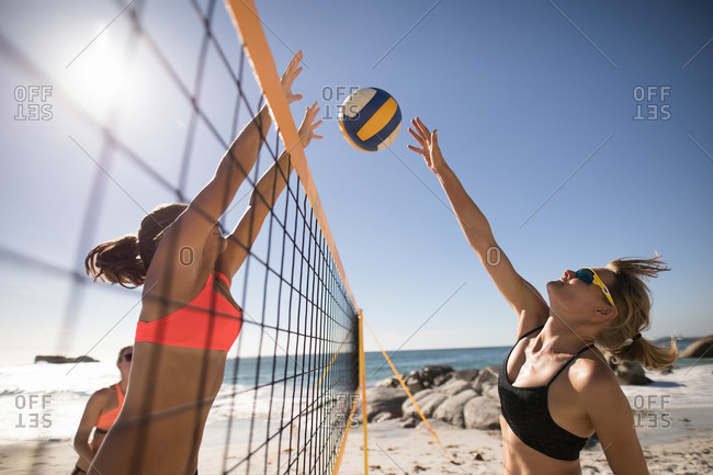 Side view of a two Caucasian female friends enjoying free time on a beach, playing beach volleyball, hitting a ball