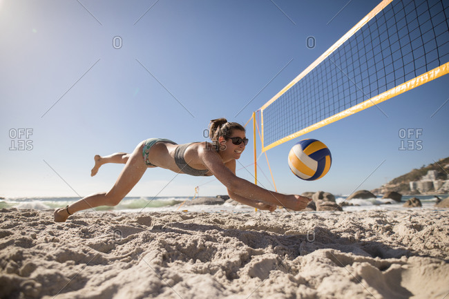 Low angle view of a Caucasian woman enjoying free time on a beach on a sunny day with blue sky, playing volleyball, diving to hit a ball