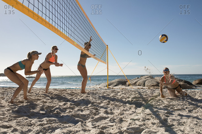 Side view of a group of Caucasian female friends enjoying free time on a beach on a sunny day with blue sky, playing beach volleyball, one of them diving to hit the ball