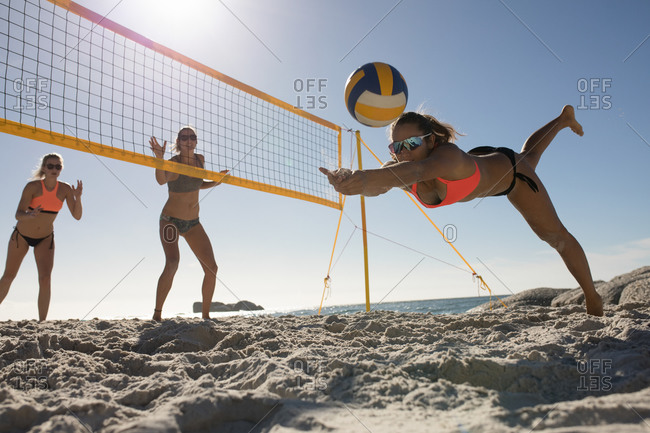 Front view of a group of Caucasian female friends enjoying free time on a beach on a sunny day with blue sky, playing beach volleyball, one of them diving to hit the ball