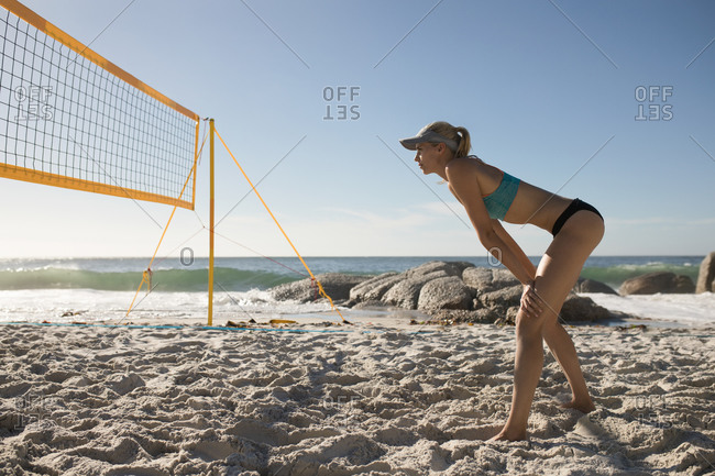 Side view of a Caucasian woman enjoying free time on a beach on a sunny day with blue sky, playing volleyball, waiting for the ball