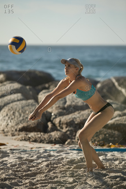 Side view of a Caucasian woman enjoying free time on a beach on a sunny day with blue sky, playing volleyball, hitting a ball