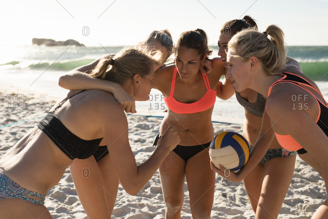 Side view of a group of Caucasian female friends enjoying free time on a beach on a sunny day, embracing each other discussing game plan, one of them holding a ball