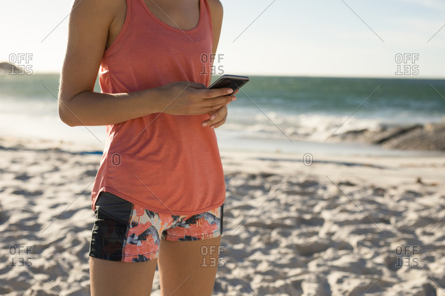Side view mid section of a Caucasian woman enjoying free time on a beach on a sunny day with blue sky, using smartphone