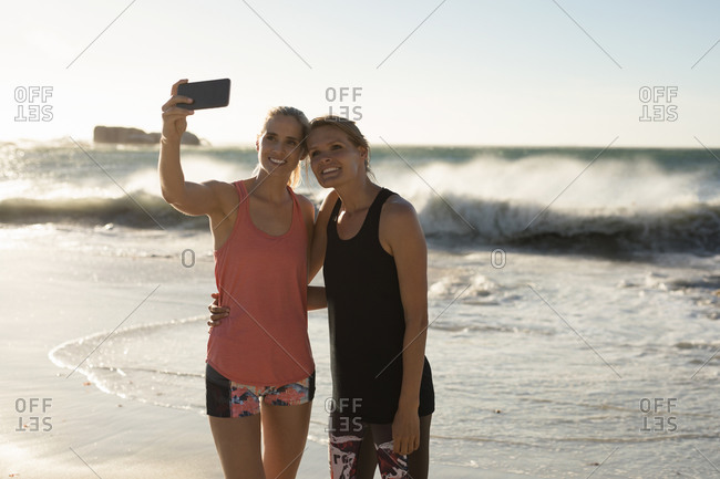 Front view of two Caucasian female friends enjoying free time on a beach on a sunny day with blue sky, taking a selfie with smartphone