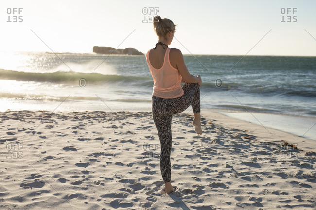 Rear view of a Caucasian woman enjoying free time on a beach on a sunny day with blue sky, practicing yoga standing with one leg up