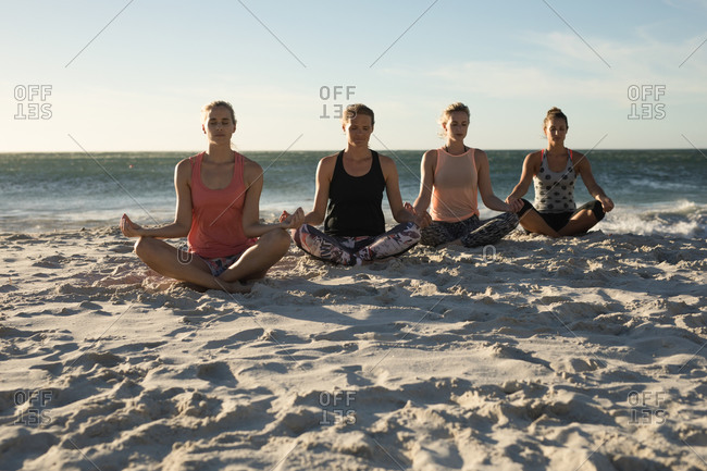 Front view of a group of Caucasian female friends enjoying free time on a beach on a sunny day with blue sky, practicing yoga sitting with legs crossed and eyes closed