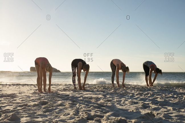 Front view of a group of Caucasian female friends enjoying free time on a beach on a sunny day with blue sky, practicing yoga bending down
