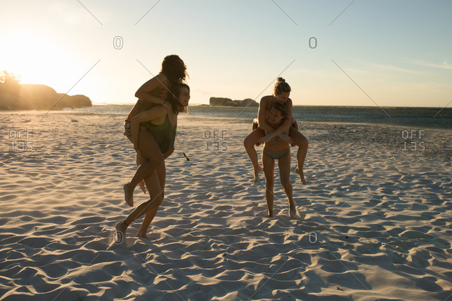 Front view of a group of Caucasian female friends enjoying free time on a beach on a sunny day, carrying each other piggyback