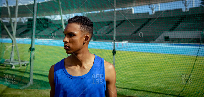 Side view of a mixed race male athlete practicing at a sports stadium, looking away from the camera. Track and Field Sports Training in Stadium.