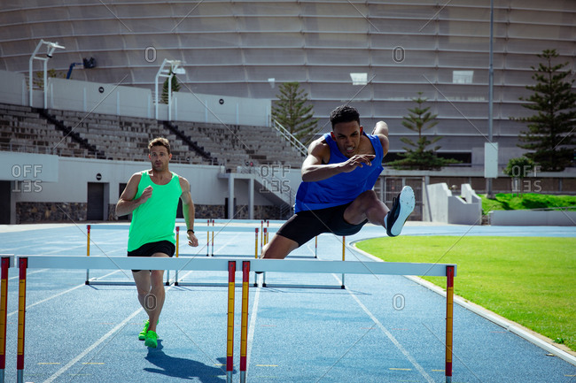 Front view of a Caucasian and a mixed race male athlete practicing at a sports stadium, racing each other on running track, hurdling