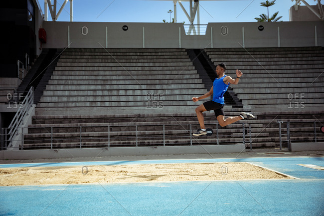 Side view of a mixed race male athlete practicing at a sports stadium, doing a long jump. Track and Field Sports Training in Stadium.
