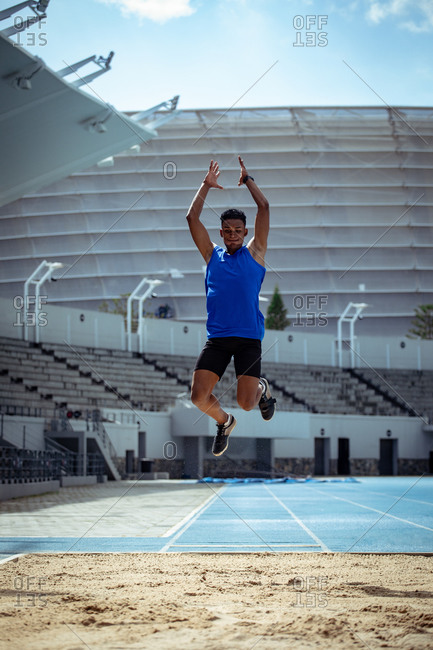 Front view of a mixed race male athlete practicing at a sports stadium, doing a long jump. Track and Field Sports Training in Stadium.