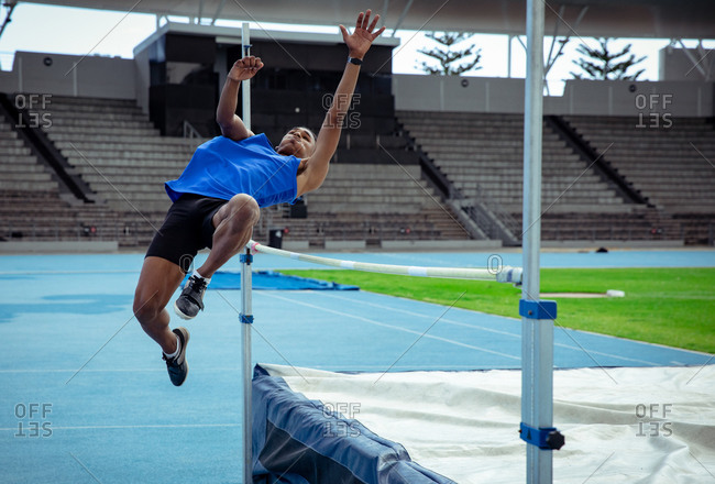 Side view of a mixed race male athlete practicing at a sports stadium, doing a high jump. Track and Field Sports Training in Stadium.