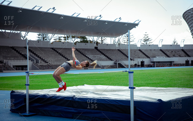 Side view of a Caucasian female athlete practicing at a sports stadium, doing a high jump. Track and Field Sports Training in Stadium.