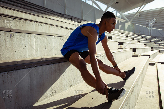 Side view of a mixed race man athlete practicing at a sports stadium, stretching at a stand, reaching his ankles