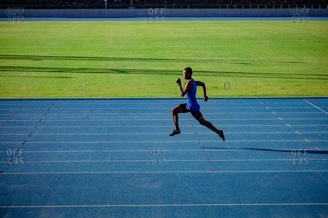 Side view of a mixed race male athlete practicing at a sports stadium, sprinting. Track and Field Sports Training in Stadium.