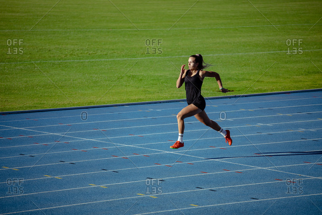 Side view of a Caucasian female athlete practicing at a sports stadium, sprinting. Track and Field Sports Training in Stadium.