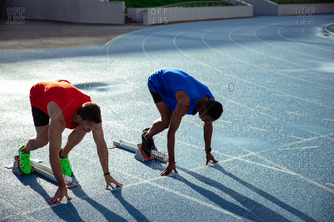Side view of a Caucasian and a mixed race male athlete practicing at a sports stadium, in position on the starting blocks, preparing to sprint