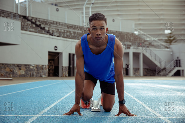 Front view of a mixed race male athlete practicing at a sports stadium, in position on the starting blocks, preparing to sprint, with his head up