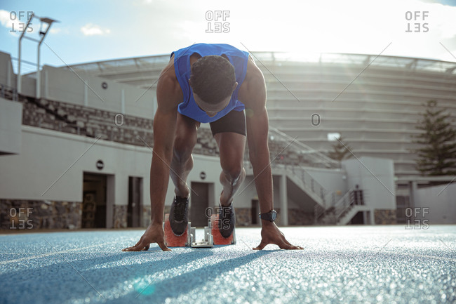 Front view of a mixed race male athlete practicing at a sports stadium, in position on starting blocks, preparing to sprint, with his head down, backlit by sunlight