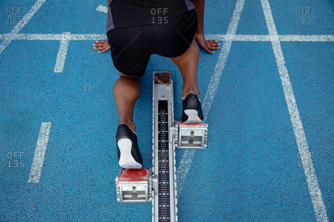 High angle close up of a mixed race male athlete practicing at a sports stadium, in position on starting blocks, preparing to sprint