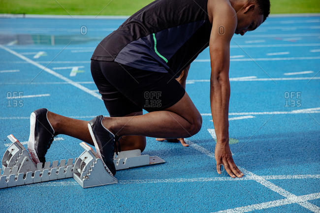 Side view of a mixed race male athlete practicing at a sports stadium, in position on starting blocks, preparing to sprint