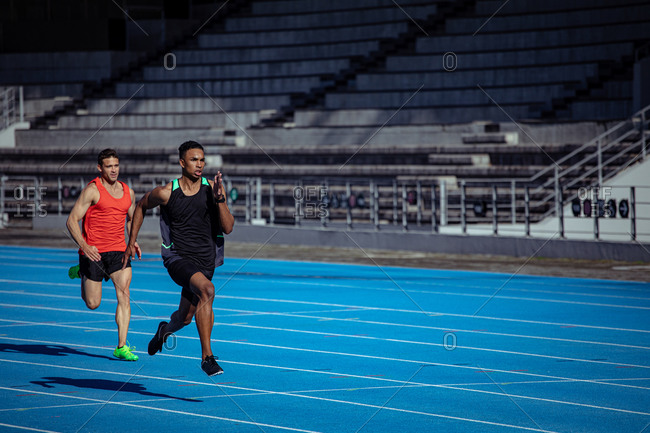 Side view of a Caucasian and a mixed race male athlete practicing at a sports stadium, racing each other on running track