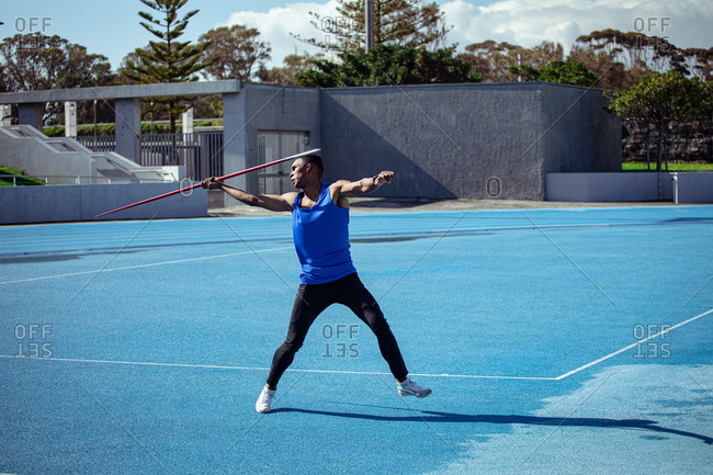 Side view of a mixed race male athlete practicing at a sports stadium, preparing to throw a javelin. Track and Field Sports Training in Stadium.